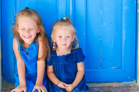Closeup of Little adorable girls sitting near old blue door in Greek village, Emporio, Santorini photo