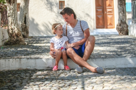 Young father with little daughters have a rest on street in old greek town photo