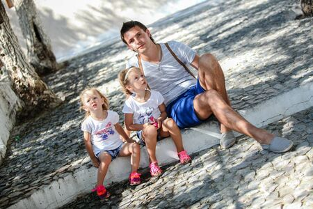 Young father and cute daughters sitting on street in old greek town photo