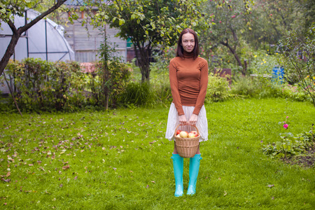 Young woman in rubber boots holding the straw basket with red apples at autumn time photo