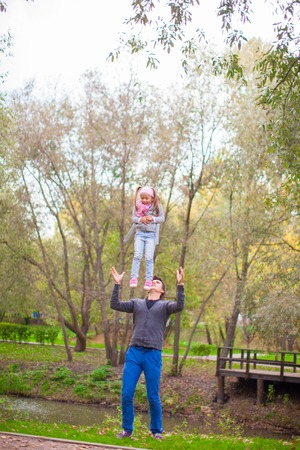 Young father with his cute little daughter have fun outdoor in the park