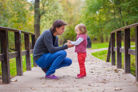 Young father with his cute little daughter in autumn park photo