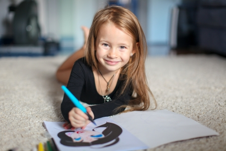 Portrait of a sweet charming young girl who draws with his coloring at home photo