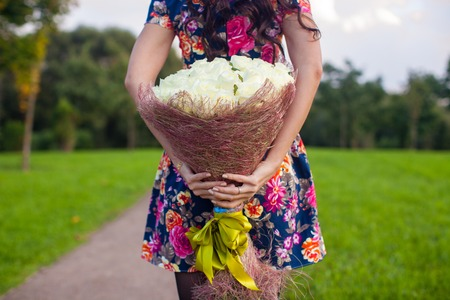 Incredibly beautiful large bouquet of white roses in the hands of a young girl in colored dress photo