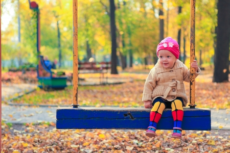 Little beautiful girl having fun on a swing in the autumn park photo