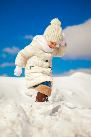 winter day: Little happy girl is walking in the snow on a sunny winter day