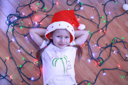 Little happy girl lies among the multi-colored lights on a wooden floor photo