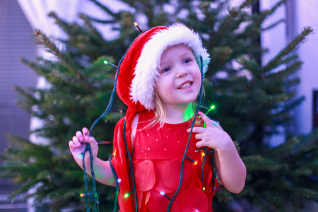 Little beautiful girl in a red dress and hat with Christmas garlands around her neck photo