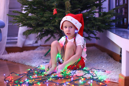 Adorable little girl in chritmas hat sitting under the New Year tree among garlands photo