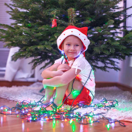 Little beautiful girl in Santa Claus hat sitting under the Christmas tree among garlands photo