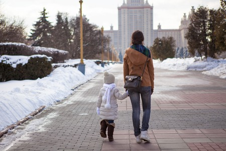 Young mother and her adorable little daughter walking on a sunny winter day photo