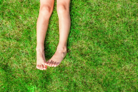 Close-up of two legs of a young girl on the grass on the lawn photo