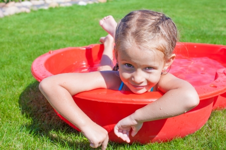 Portrait of relaxing charming little girl enjoying her vacation in small pool photo