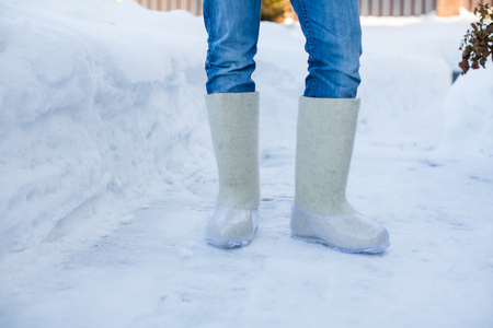 Close-up of warm boots for men s feet on the white snow photo