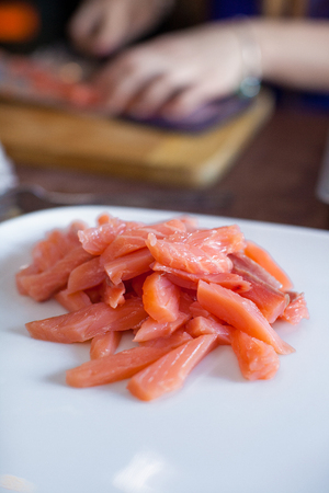 Cut pieces of salmon on a white plate photo