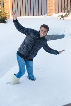 Young man in winter boots fell into a deep white snow photo