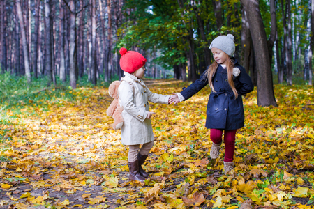 Two beautiful adorable girls walking in the fall forest at warm sunny autumn day Stock Photo - 22803936