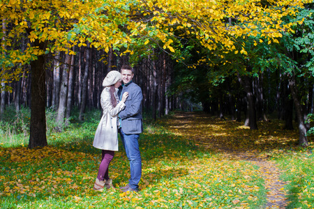 Young couple in love on the big autumn meadow under large maple tree at sunny fall day Stock Photo - 22804434