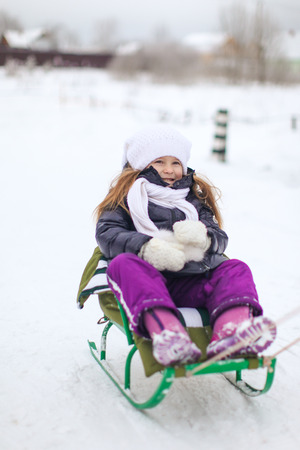 Adorable little girl on a sled at winter sunny day photo
