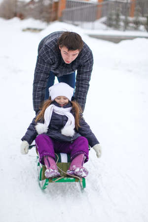 to go sledding: Young father with his baby daughter in a sleigh ride and enjoy sunny winter day Stock Photo