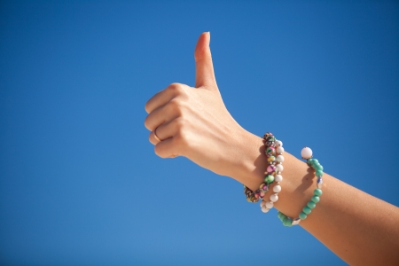powe: Thumbs up sign on a womans hand against the turquoise sea