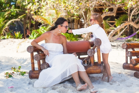 Young mother and her little daughters smelling flowers on tropical beach photo