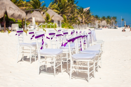 White wedding chairs decorated with purple bows on sandy beach photo