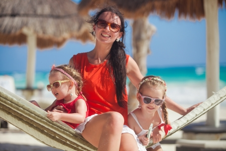 Young mom and little daughter relaxing in hammock on tropical vacation photo