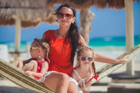 Young mother and her little daughters having rest in a hammock on Caribbean white beach photo