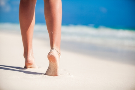 Women's beautiful smooth legs on white sand beach photo