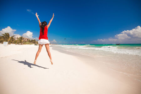 raises: Young beautiful woman raises her arms up on the beach