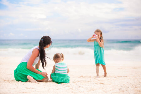 Happy caucasian family enjoying time together at the white beach photo