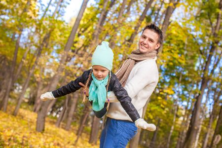 Little cute girl with happy father having fun in autumn park on a sunny day photo