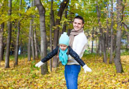 Happy dad and his little daughter having fun in the park on a sunny autumn day