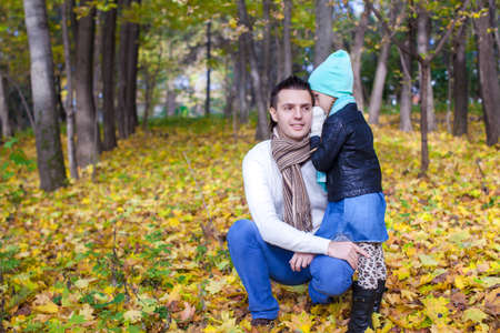 Young father and his cute little daughter whispering in autumn park photo
