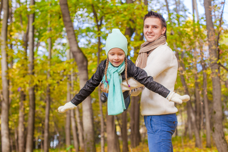 Cute little girl with happy daddy enjoy their autumn vacation on a sunny day photo