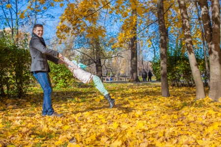 Adorable little girl with happy dad having fun in autumn park on a sunny day photo