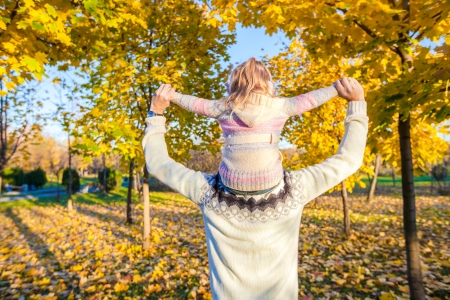 Back view of Little girl riding on fathers shoulders in autumn park Stock Photo