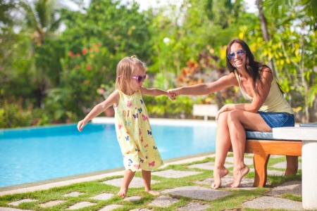 Young mother and her little daughter have fun near the swimming pool Фото со стока