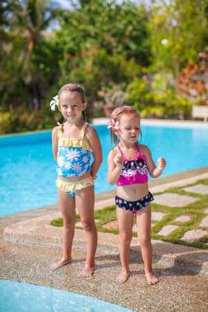 Two little sisters in nice swimsuits near swimming pool at tropical resort photo