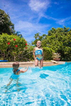 Little girls jumping and having fun in swimming pool photo