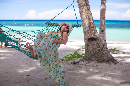 Happy young woman lying in the hammock on tropical beach photo