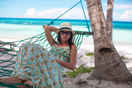 Happy young woman relaxing in the hammock on sunny day photo