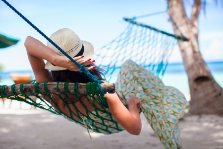 Rear view of Young woman enjoying a sunny day in the hammock Фото со стока