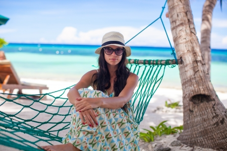 Adorable young woman lying in the hammock on tropical beach photo