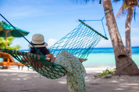 Adorable young woman lying in the hammock on tropical beach Stock Photo - 23577521