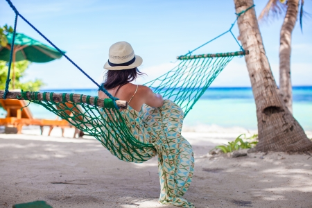 Back view of Young woman enjoying a sunny day in the hammock photo