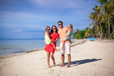 Young beautiful family of four enjoyed relaxing on the beach photo