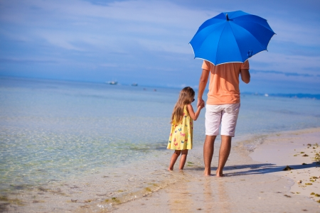 Young father and his little daughter walking under a blue umbrella on white sand beach photo