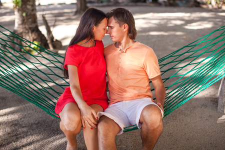 Portrait of Young loving couple in a hammock at white sand beach photo
